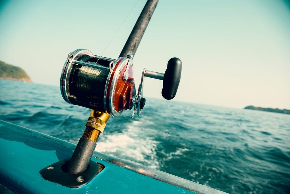 Close up of fishing rod and reel attached to the rear of a boat.