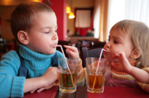two kids sipping on a drink