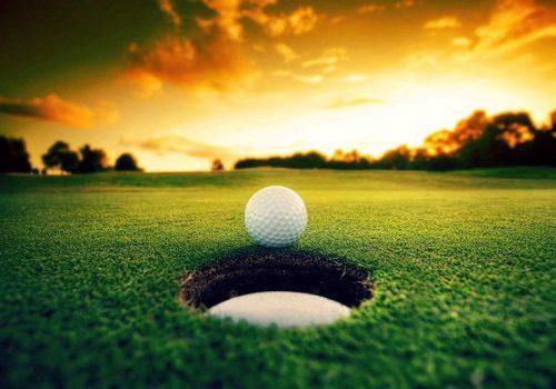 Golf ball on the edge of a hole.